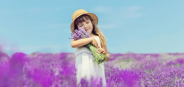 Un bambino in un campo fiorito di lavanda.