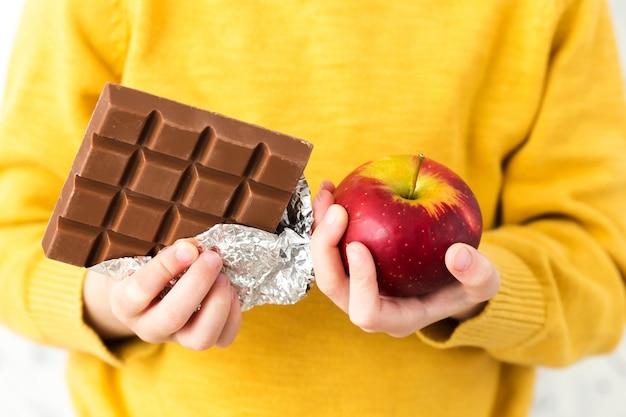 Un bambino in un maglione giallo in possesso di una mela e cioccolato.
