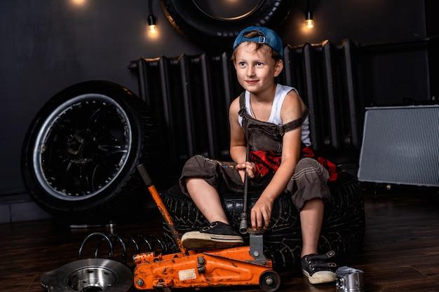 Un bambino in un'officina riparazioni auto tra ruote e parti di automobili