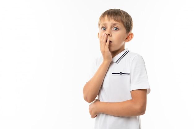 Un bambino in una camicia bianca, pantaloncini blu con capelli biondi, maglietta bianca mostra che è spaventato