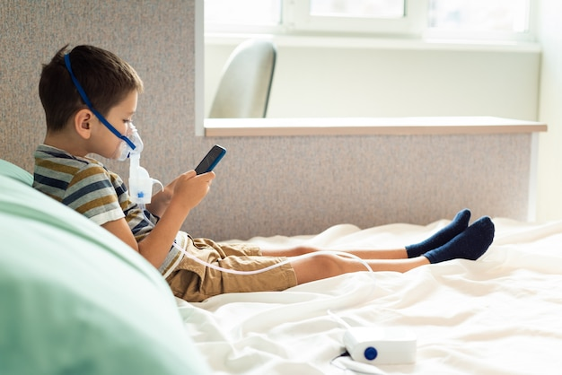 Un bambino in una maschera di ossigeno con un nibulizer gioca su smartphone