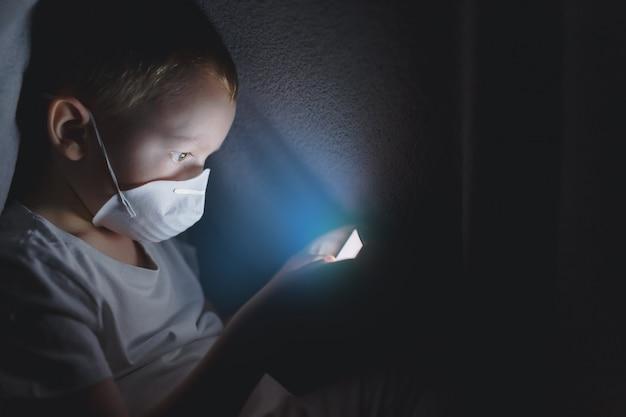 Un bambino in una maschera protettiva sotto una coperta che gioca con uno smartphone, seduto su internet. il concetto di trascorrere del tempo in isolamento sicuro.