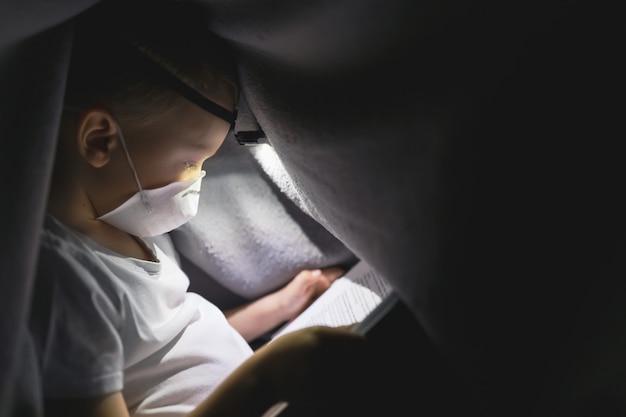 Un bambino in una maschera protettiva sotto una coperta che legge un libro con una torcia. il concetto di trascorrere del tempo in isolamento sicuro.