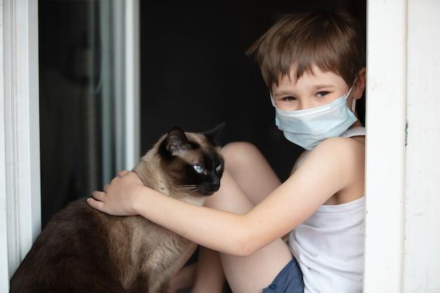 Un bambino in una mascherina medica si siede su un davanzale con un gatto