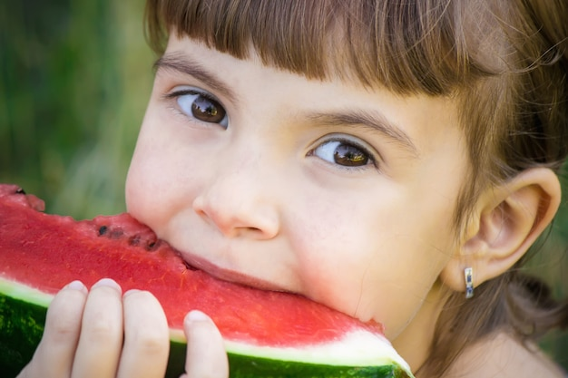 Un bambino mangia anguria. messa a fuoco selettiva cibo