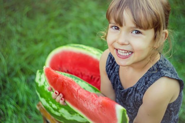 Un bambino mangia l'anguria. messa a fuoco selettiva natura.