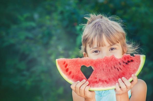 Un bambino mangia l'anguria.