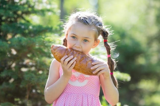 Un bambino morde il pane in natura.