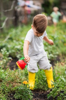 Un bambino nel giardino innaffia i fiori con un annaffiatoio.