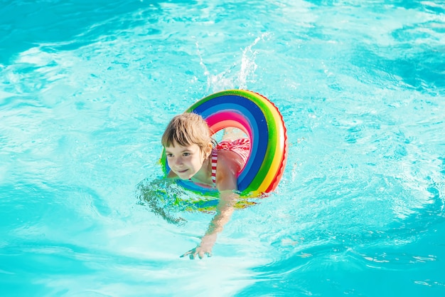 Un bambino nuota in una piscina con un salvagente. messa a fuoco selettiva