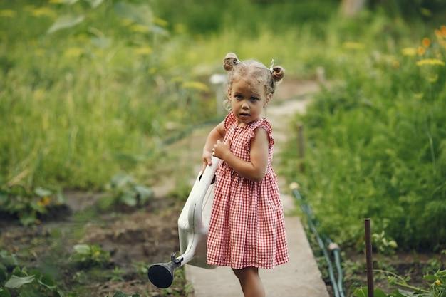 Un bambino piccolo con un annaffiatoio con fiori versare. ragazza con un imbuto. bambino in un vestito rosa.