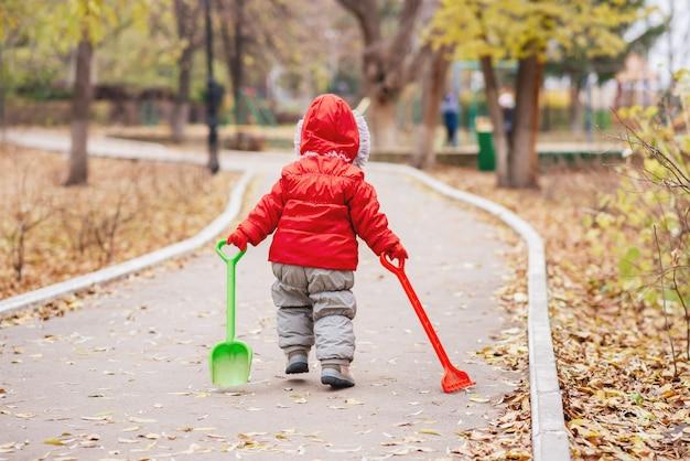 Un bambino piccolo con un rastrello e una pala cammina nel parco