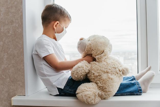 Un bambino piccolo con una maschera siede a casa in quarantena e guarda fuori dalla finestra in un posto con un orsacchiotto. prevenzione di coronavirus e covid - 19. concetto