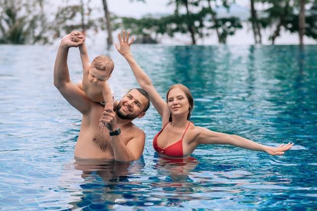Un bambino piccolo e genitori divertirsi in piscina durante le vacanze estive