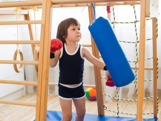 Un bambino piccolo è impegnato nel pugilato su un complesso sportivo di legno in casa.