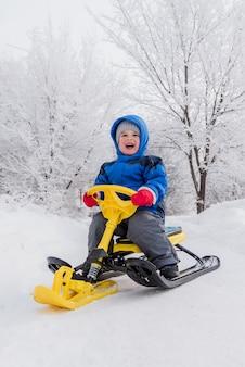 Un bambino piccolo è seduto su uno scooter da neve in inverno