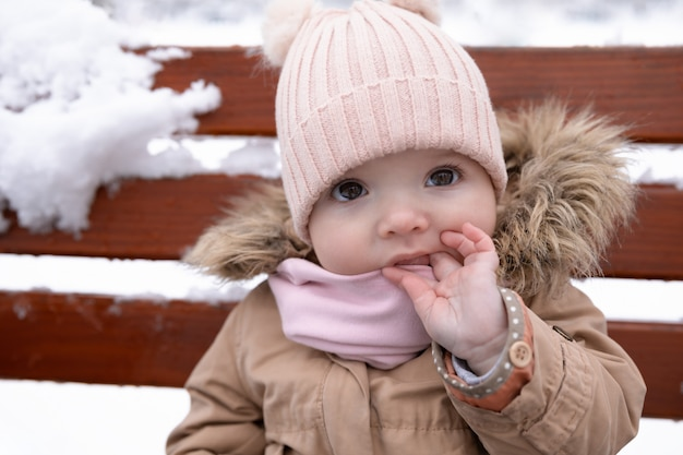 Un bambino piccolo è seduto sulla panchina.