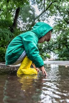 Un bambino piccolo gioca seduto in una pozzanghera in caso di pioggia