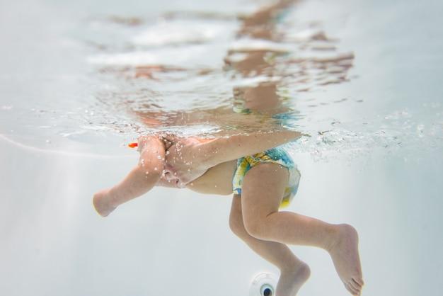 Un bambino piccolo nuota sott'acqua.