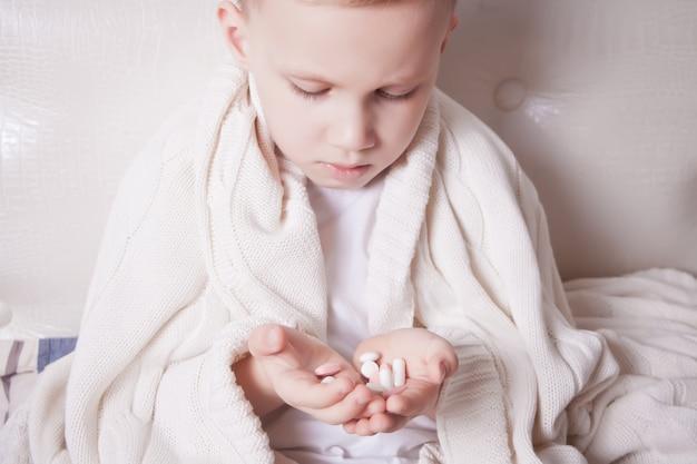 Un bambino piccolo seduto in un letto e con in mano le sue pillole di palma