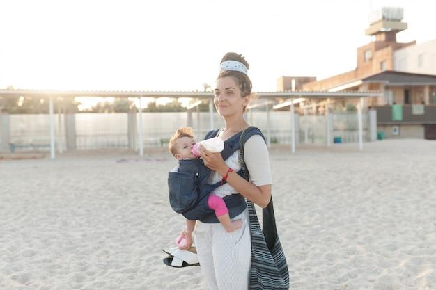 Un bambino piccolo si siede in uno zaino e cammina con la madre in riva al mare.