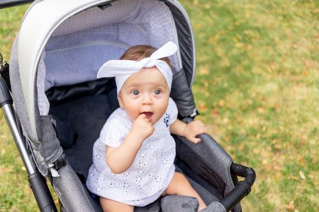 Un bambino piccolo una ragazza di 7 mesi si siede in un passeggino in estate con un vestito bianco e guarda la telecamera