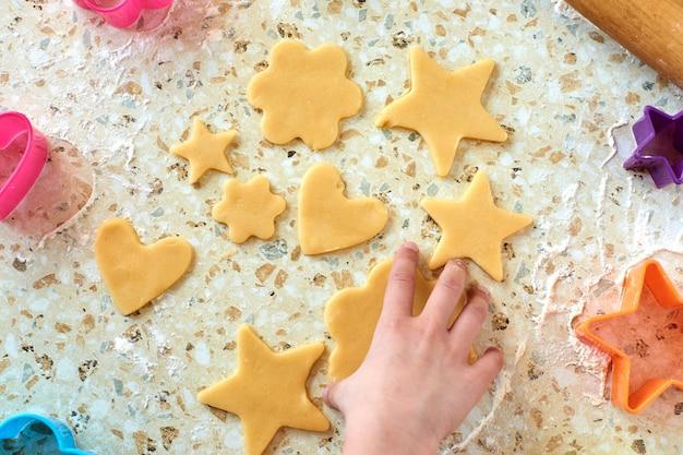 Un bambino produce biscotti, stende la pasta e usa i moduli per preparare i biscotti.