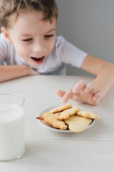 Un bambino ruba da un piatto di biscotti fatti in casa appena sfornati