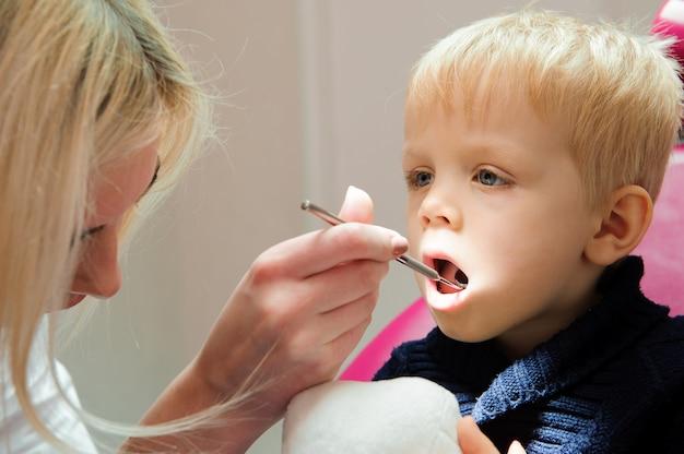 Un bambino seduto su una sedia dentale, stomatologo.