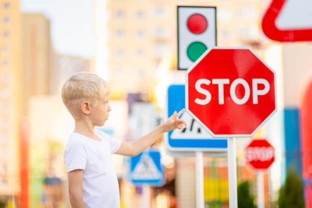 Un bambino si trova a un segnale di stop e tiene le mani in croce