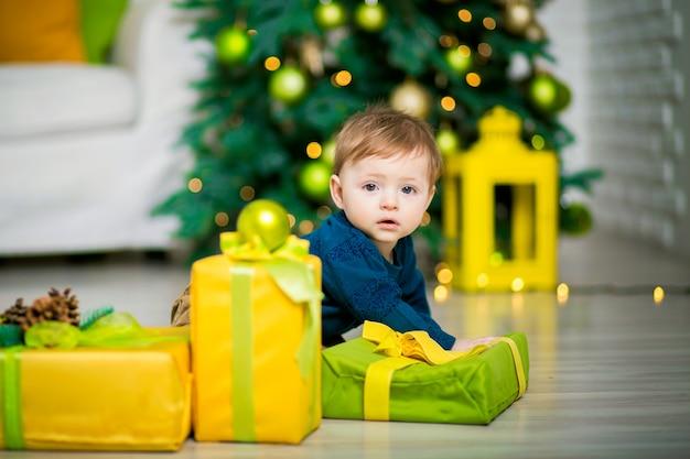 Un bambino sotto l'albero di natale giace, accanto a scatole regalo di natale.