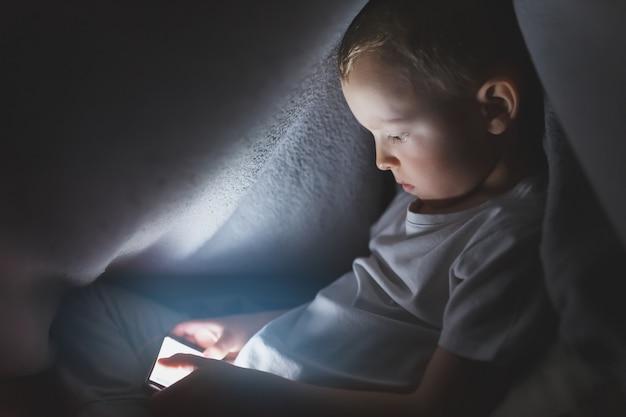 Un bambino sotto una coperta che gioca con uno smartphone, seduto su internet. il concetto di trascorrere del tempo in isolamento sicuro.