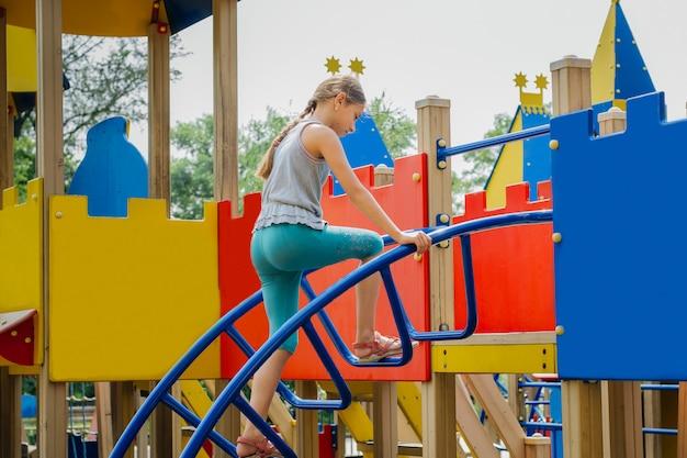 Un bambino sta giocando in un parco giochi all'aperto.