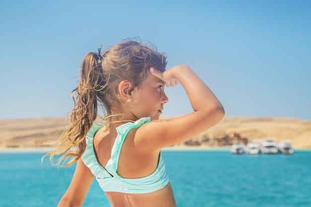 Un bambino su uno yacht a vela sul mare.