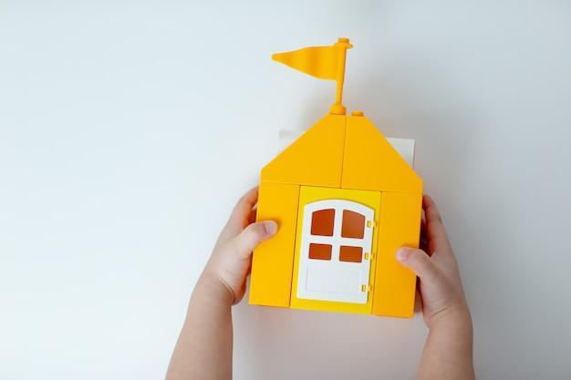 Un bambino tiene lego house, resta a casa, stai al sicuro. casa giocattolo gialla con la famiglia lego. un autoisolamento del bambino durante il virus.