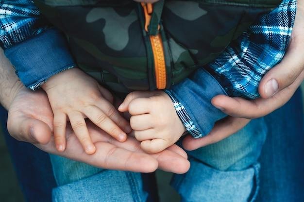 Un bambino tra le braccia di suo padre per la strada