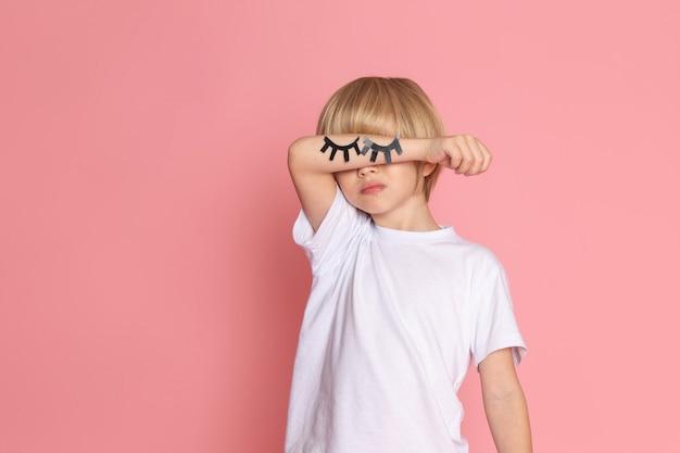 Un bambino vista frontale in maglietta bianca con le mani chiuse gli occhi sulla scrivania rosa