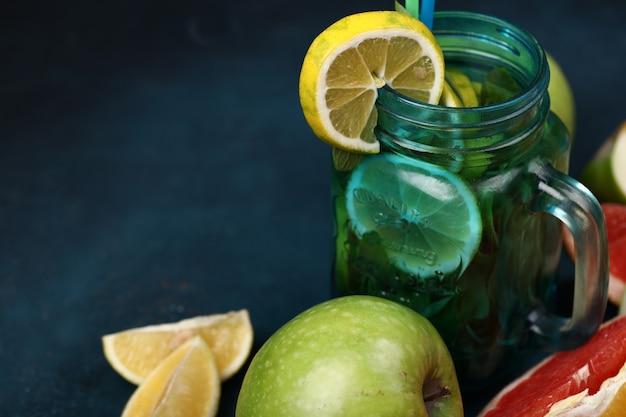 Un barattolo blu di mojito cocktail con fettine di limone.