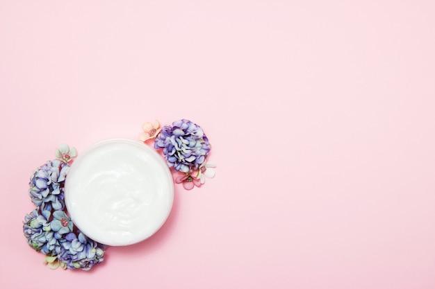 Un barattolo di crema con fiori rosa