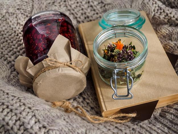 Un barattolo di marmellata di lamponi con erbe secche utili e un libro si trovano su una coperta di lana