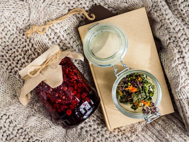 Un barattolo di marmellata di lamponi, erbe secche e un libro giacciono su una coperta di lana.