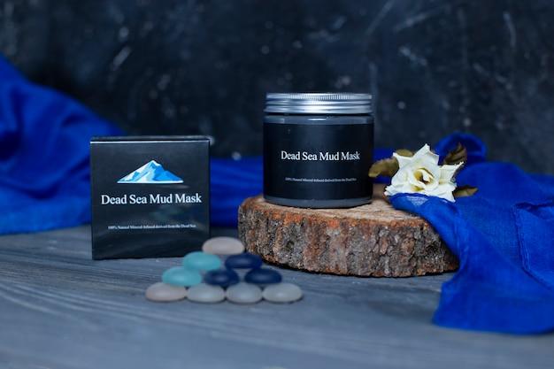 Un barattolo di maschera di fango del mar morto naturale per la cura della pelle con cappuccio argentato e scatola quadrata