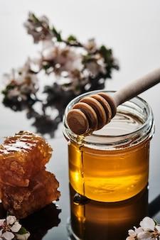 Un barattolo di miele con nido d'ape e un bastone