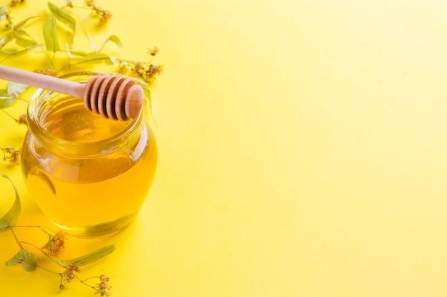 Un barattolo di miele liquido dai fiori di tiglio e un bastone con miele su sfondo giallo. copia spazio