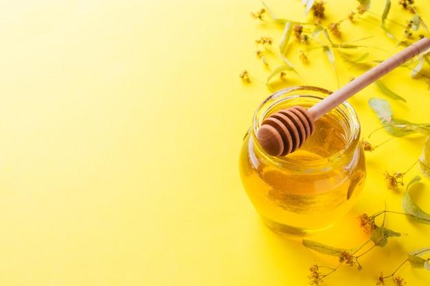 Un barattolo di miele liquido dai fiori di tiglio e un bastone con miele sulla superficie gialla. copia spazio