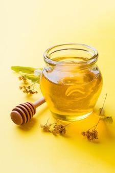 Un barattolo di miele liquido dai fiori di tiglio e un bastone con miele sulla superficie gialla.