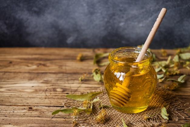Un barattolo di miele liquido di fiori di tiglio e un bastoncino di miele su una superficie scura. copia spazio