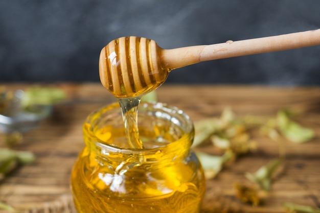Un barattolo di miele liquido di fiori di tiglio e un bastoncino di miele su una superficie scura.
