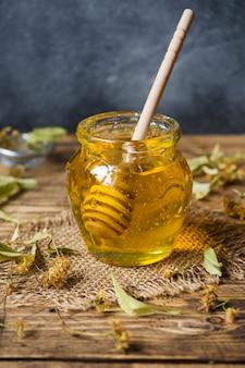 Un barattolo di miele liquido di fiori di tiglio e un bastoncino di miele