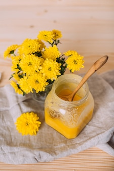 Un barattolo di miele solido e fiori sul tavolo di legno.